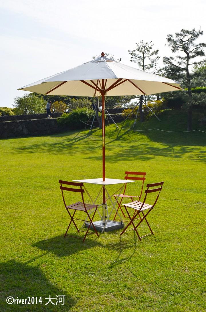 大片的草坪上摆放了阳伞和桌椅供游客休息.